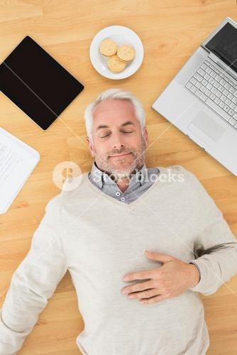Man sleeping with electronics and biscuits on parquet floor