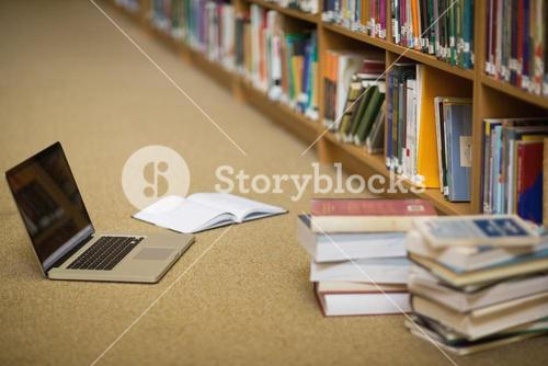 Laptop and books on the library floor