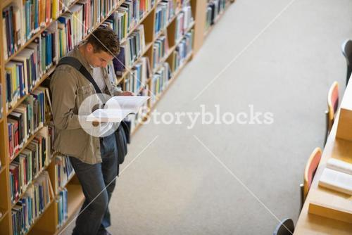 Student reading a book from shelf standing in library