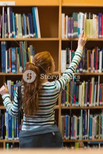Redhead student taking book from shelf in library