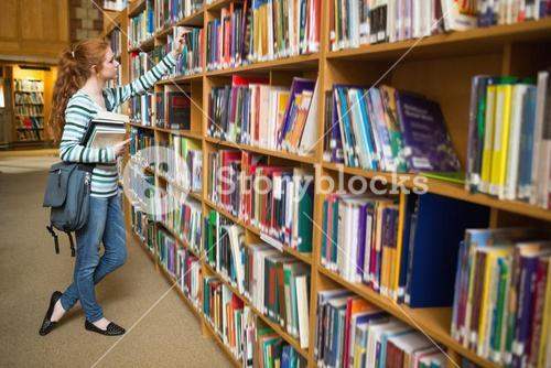 Redhead student taking book from shelf in the library