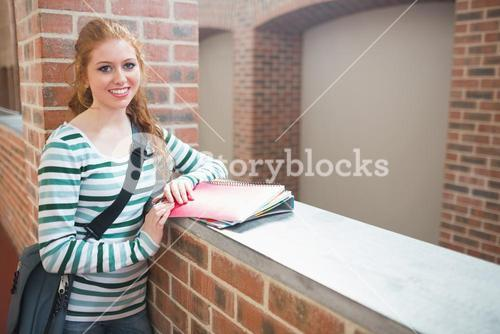 Redhead student smiling at camera in the corridor