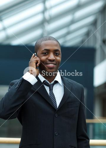 Businessman on phone and smiling at the camera