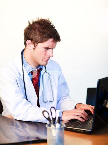 Thoughtful young doctor working on a computer