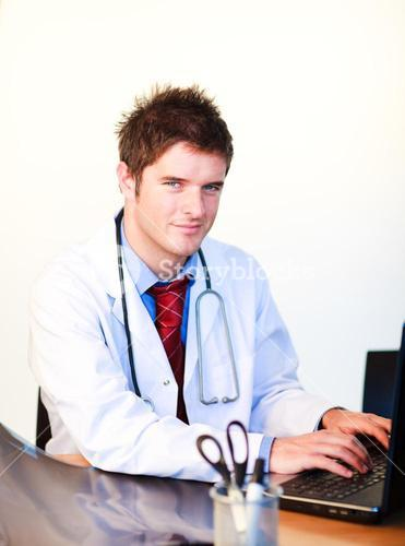 Smiling young doctor working on a computer