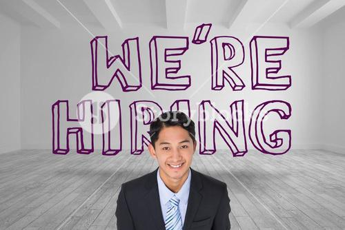 Smiling businessman standing in front of were hiring graphic