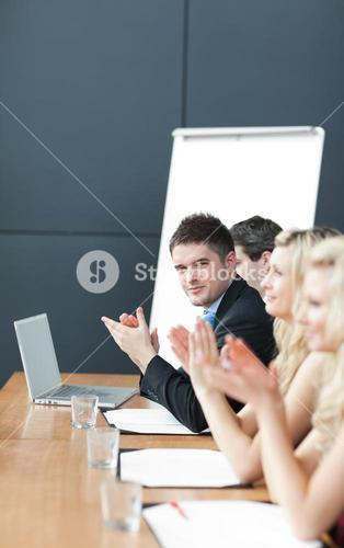 Business team at a presentation clapping