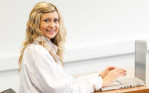 Beautiful female surgeon working on a laptop
