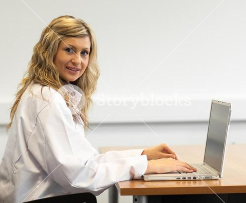 Radiant female surgeon working on a laptop