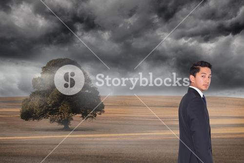 Composite image of frowning businessman looking at camera