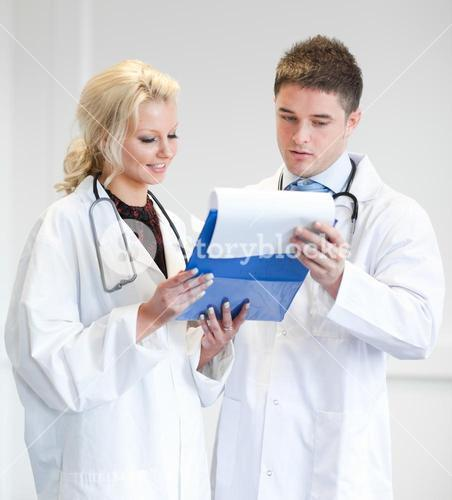 Two nice doctors looking at a report