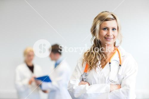 Pretty female surgeon with her team behind her