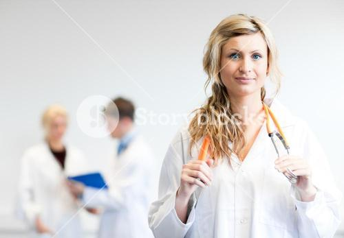 Delighted female surgeon with her team behind her
