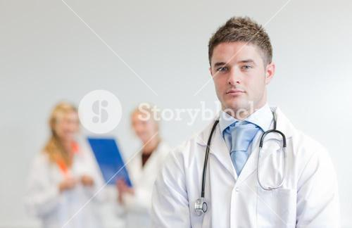 Selfassured male surgeon with his team behind him