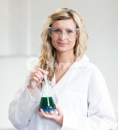 Woman in lapcoat looking at chemicals