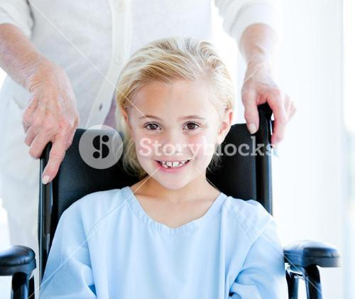 Adorable little girl sitting on a wheelchair