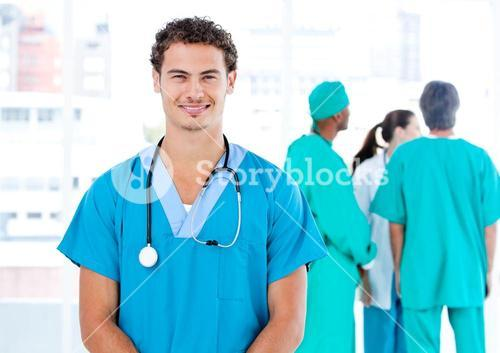 Handsome male doctor looking at the camera while his medical partners talking together