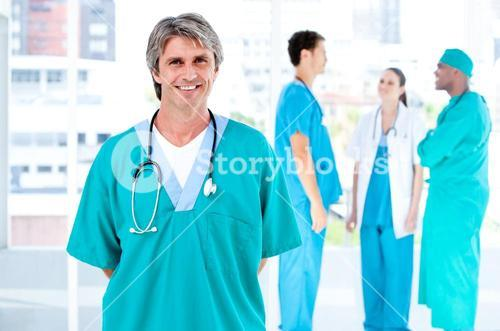 Joyful male doctor looking at the camera while his medical partners talking together