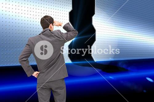 Composite image of businessman standing hand on hip