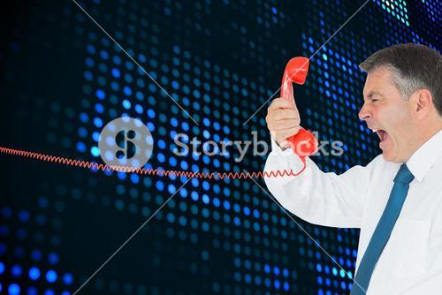 Composite image of businessman screaming directly into the handset