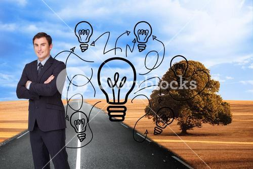 Composite image of young businessman standing crossarmed