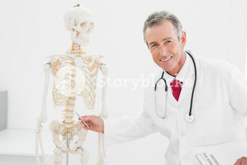 Smiling doctor explaining the spine in office