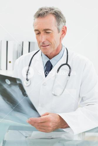 Doctor looking at xray picture of lungs in medical office