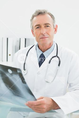 Confident doctor with xray picture of lungs in medical office