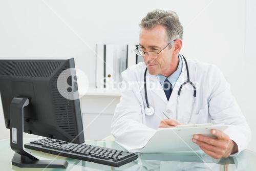 Doctor with report looking at computer monitor at medical office