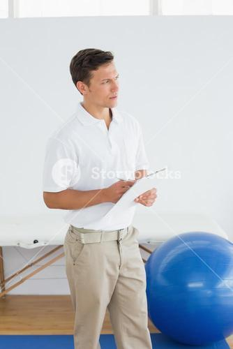 Thoughtful trainer with clipboard in gym at hospital