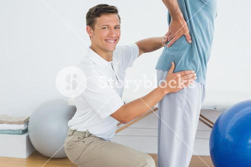 Male therapist massaging mans lower back at gym hospital