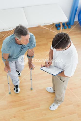 Therapist discussing reports with a disabled patient in gym hospital