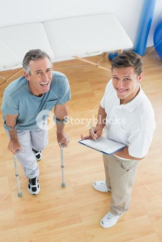 Male therapist discussing reports with a disabled patient in gym hospital