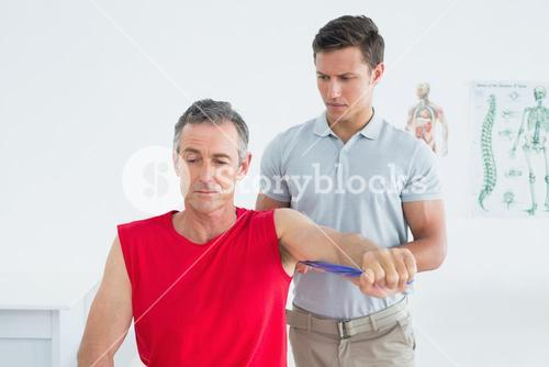 Male physiotherapist examining a mature mans arm