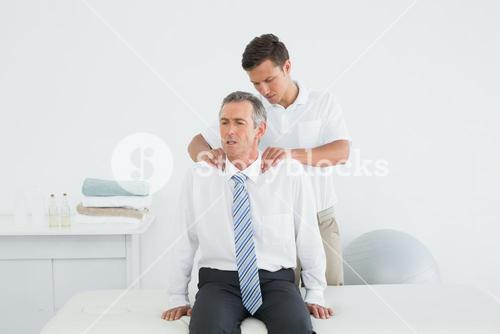 Chiropractor massaging a mature patients shoulder