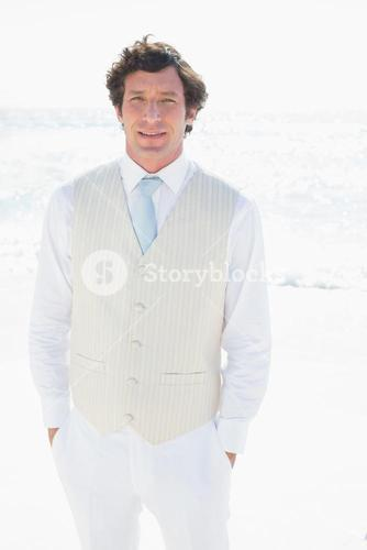 Groom smiling at camera with hands in pockets