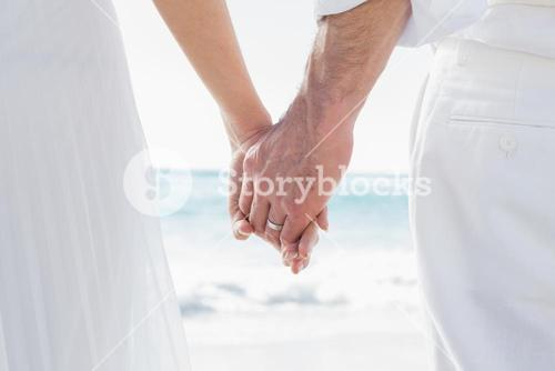 Bride and groom holding hands close up