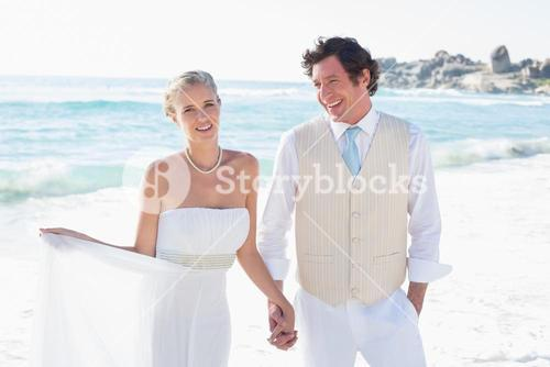 Newlyweds walking hand in hand and smiling