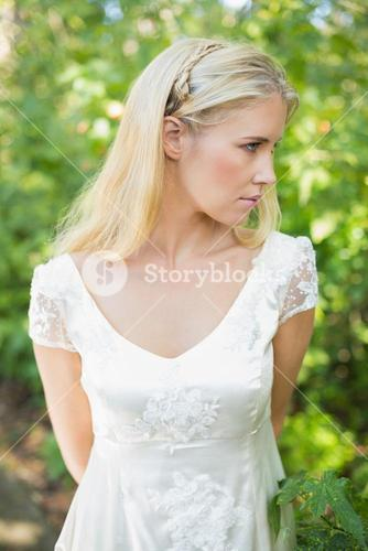 Content beautiful blonde bride with hands behind back