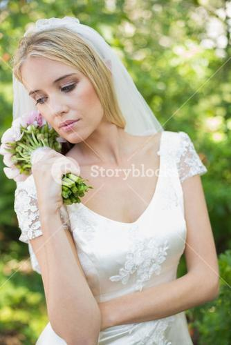 Content bride holding her bouquet wearing a veil