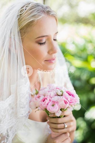Content bride wearing veil holding bouquet with eyes closed