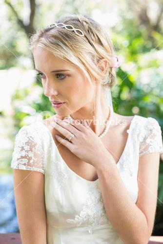 Content blonde bride with hand on chest