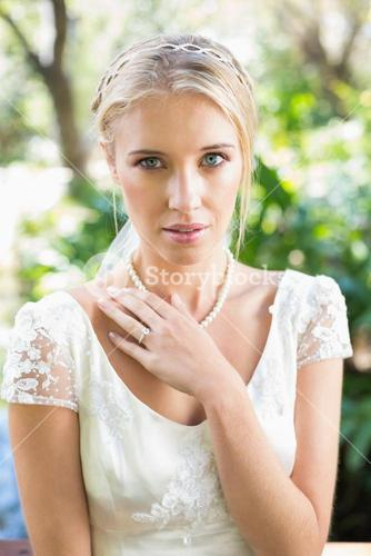 Content blonde bride with hand on chest looking at camera