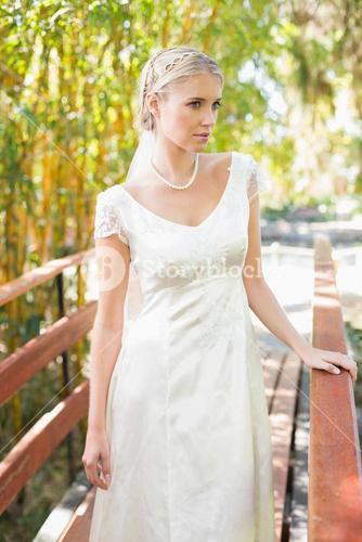 Content blonde bride in pearl necklace standing on a bridge