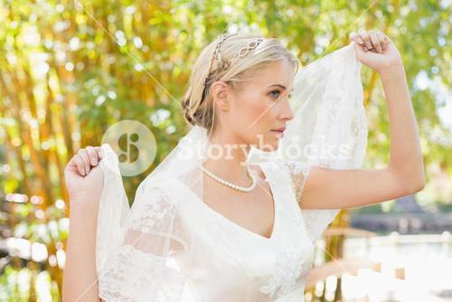 Content blonde bride holding her veil out