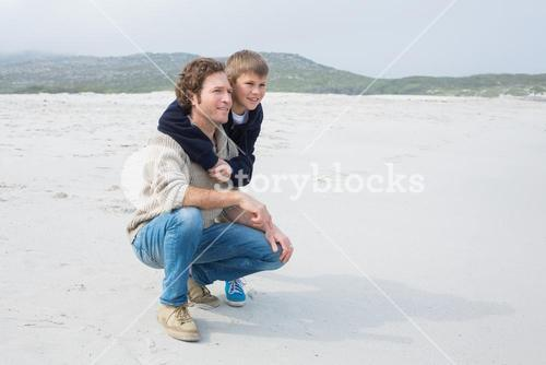 Side view of a casual man and son relaxing at beach