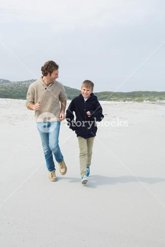 Young man and son jogging at beach
