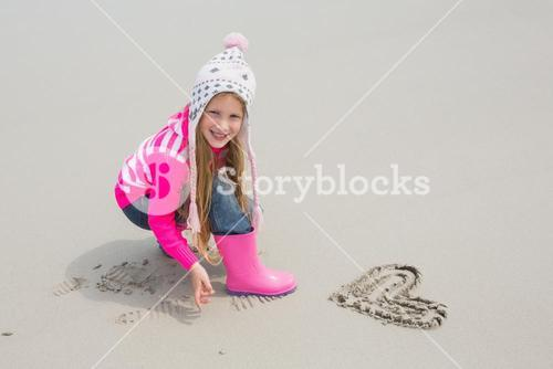 Girl in warm clothing with drawn heart shape on sand at beach