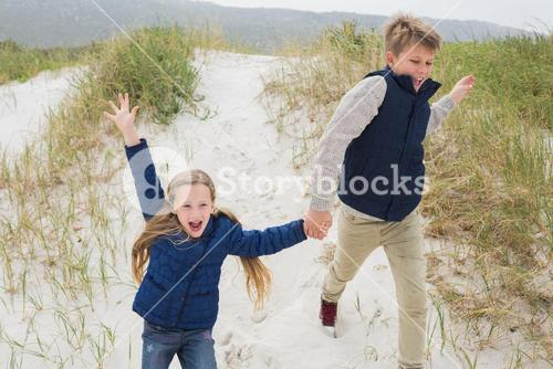 Happy siblings running hand in hand at beach