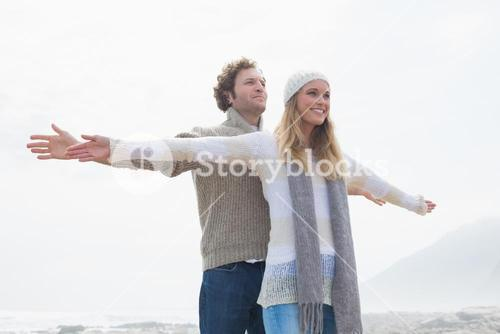 Happy casual young couple stretching hands out